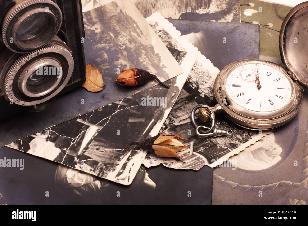 Old photo camera, old pocket watch and old photos - Stock Image