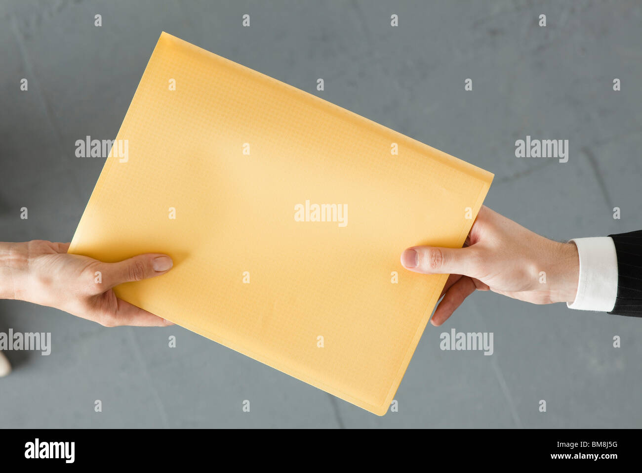 Handing colleague large brown envelope - Stock Image