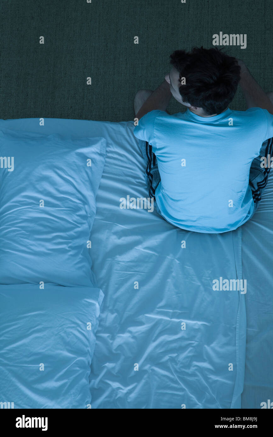 Man sitting on bed unable to sleep - Stock Image