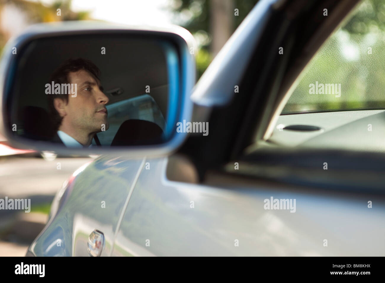 Reflection of car driver seen in side-view mirror - Stock Image