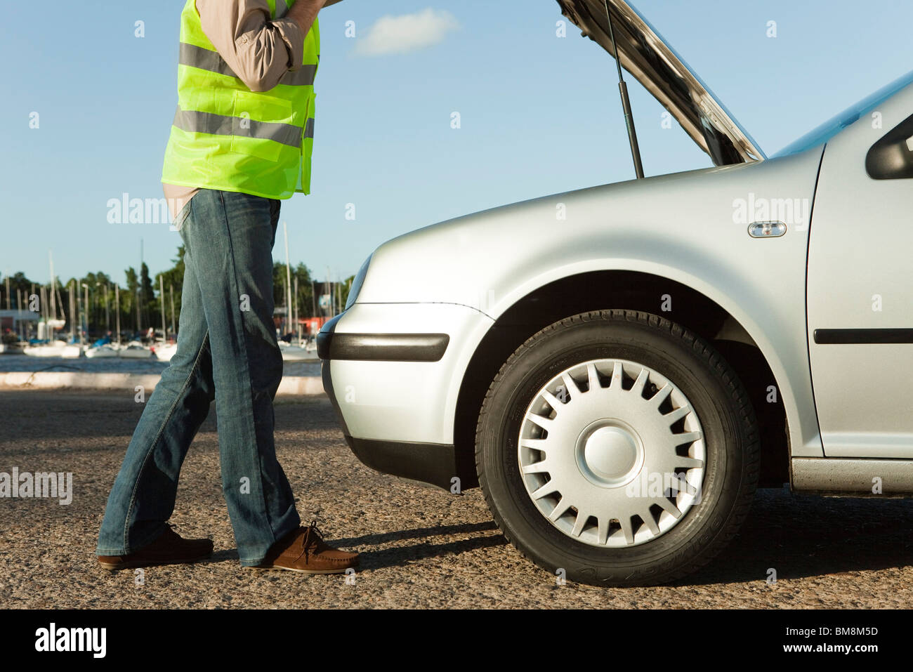 Mechanic evaluating car breakdown on side of road Stock Photo