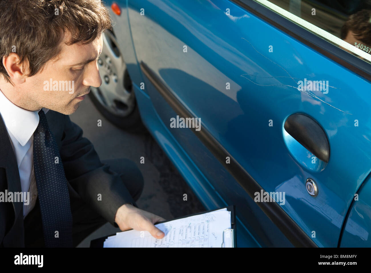 Insurance adjuster examining damage to car exterior - Stock Image