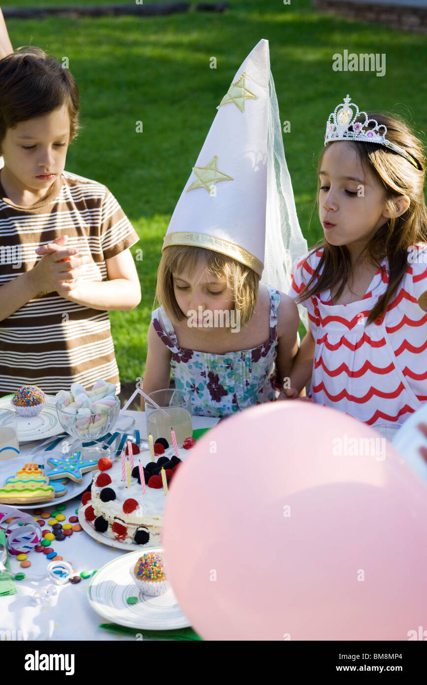 Girl Blowing Out Candles On Birthday Cake At Outdoor Birthday Party