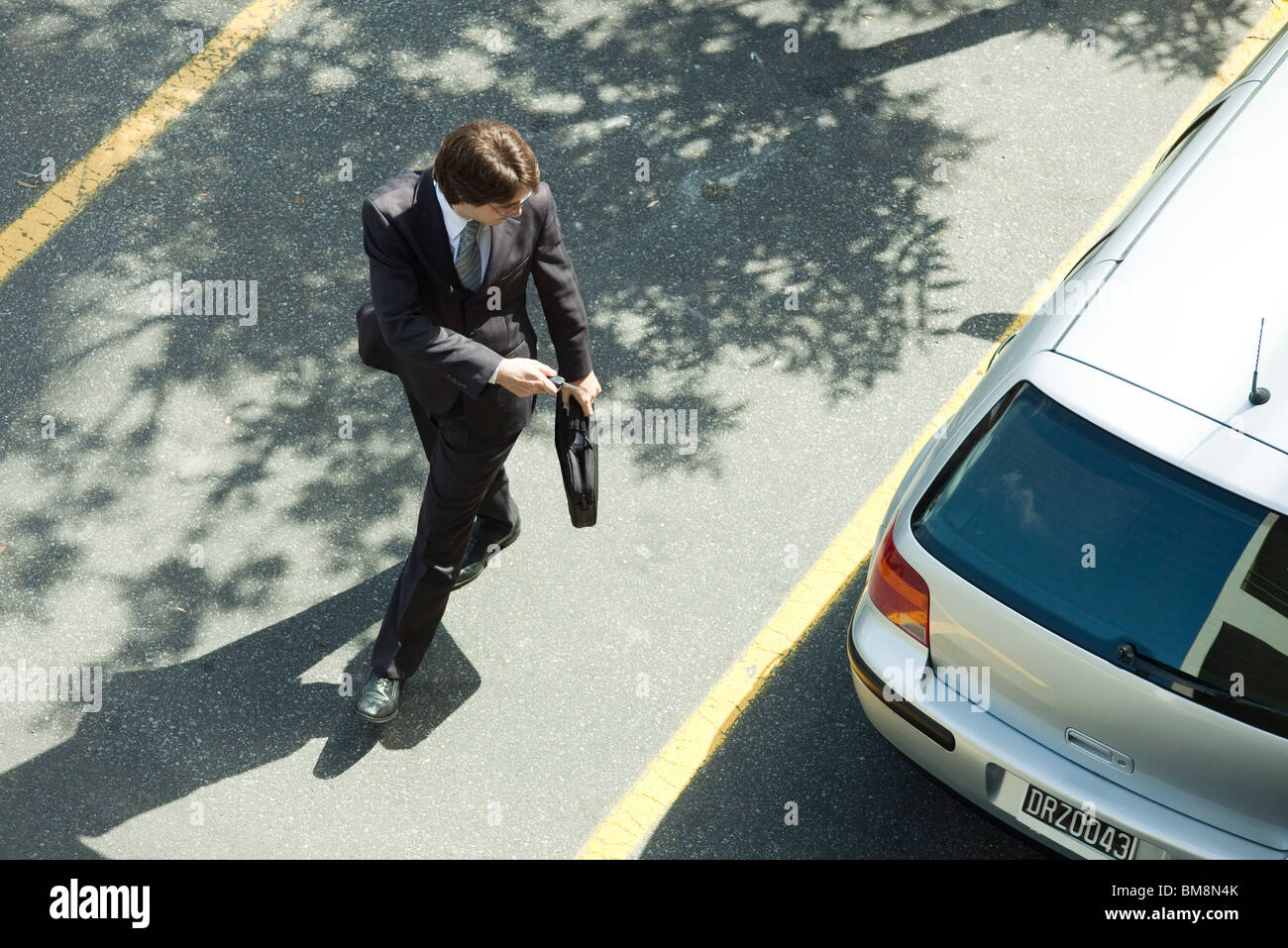 Man locking car doors using key remote as he walks away & Man locking car doors using key remote as he walks away Stock Photo ...