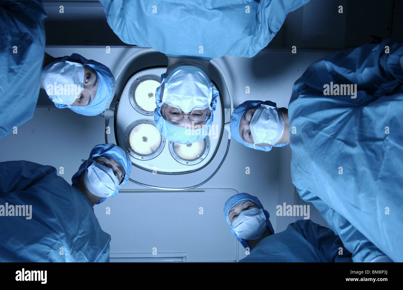 Five surgeons from operating table Stock Photo