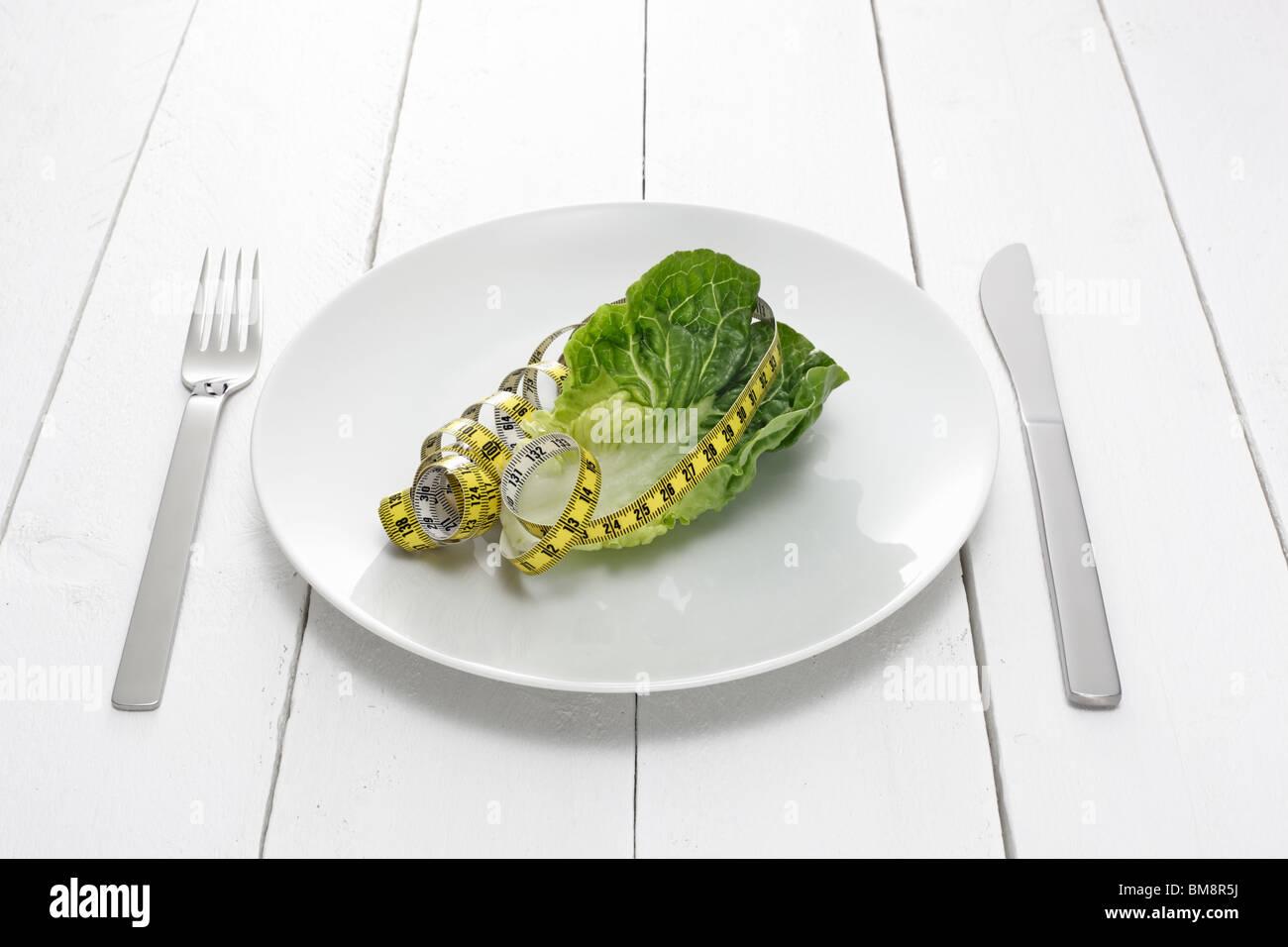 Teller mit Salatblatt und Massband - Stock Image