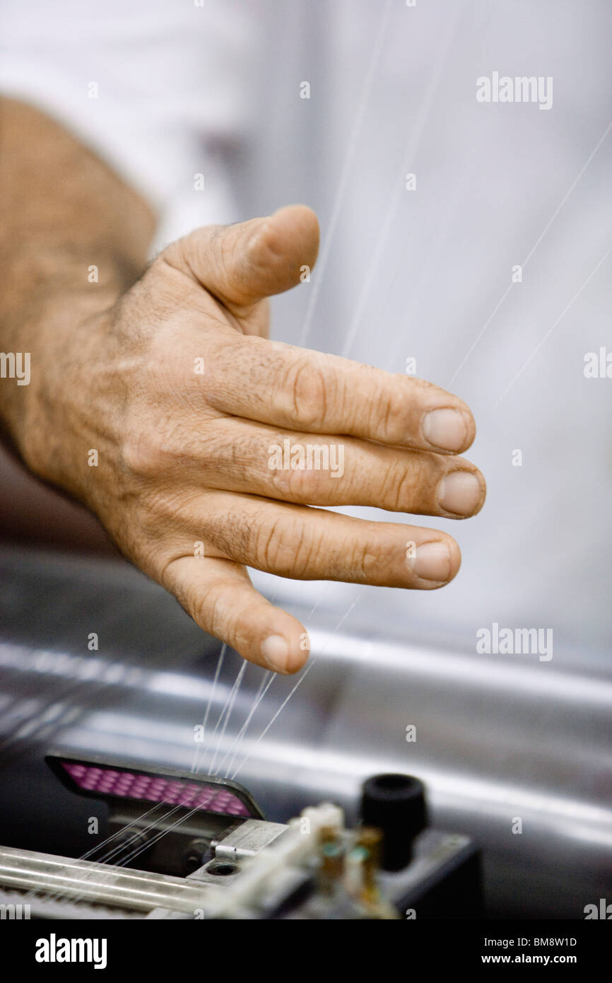 Machinist checking thread tension on loom in weaving mill - Stock Image
