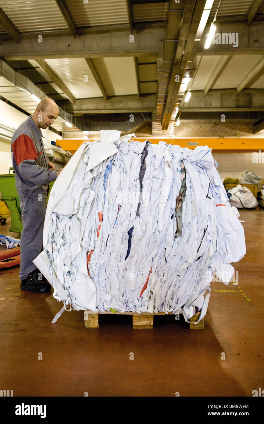 A machinist writes weight on a bale of PVC sheeting after weighing it - Stock Image