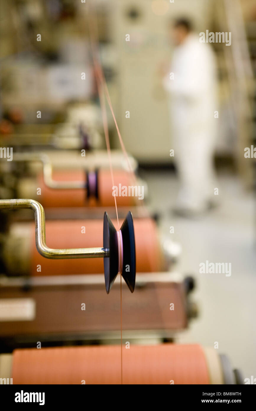 Recyclable composite textile fabrication department of factory, machinist working on thread coating machine - Stock Image