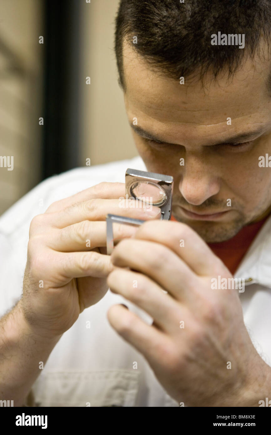 Recyclable composite textile fabrication department of factory, worker using a pick counter to inspect thread - Stock Image
