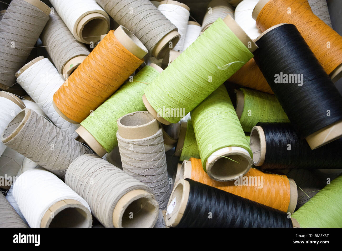 Recyclable composite textile fabrication department of factory, reels of excess coated thread - Stock Image