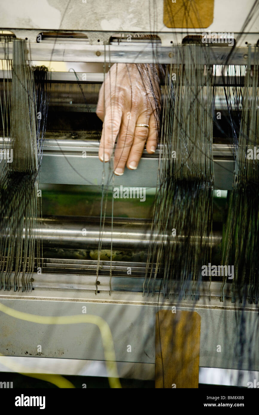 Fabric coating plant, weaving department, mechanist preparing weaver's reed on loom - Stock Image