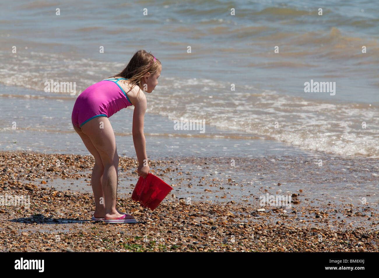 young girl in swimsuit with bucket on beach at edge of sea filling bucket - Stock Image
