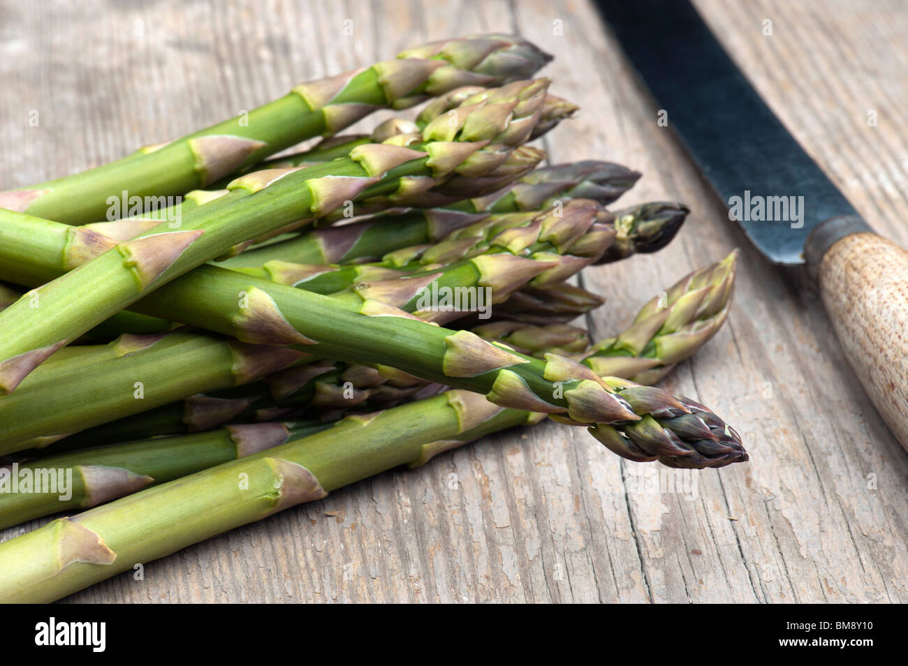 Fresh Asparagus Laid On A Wooden Kitchen Table - Stock Image