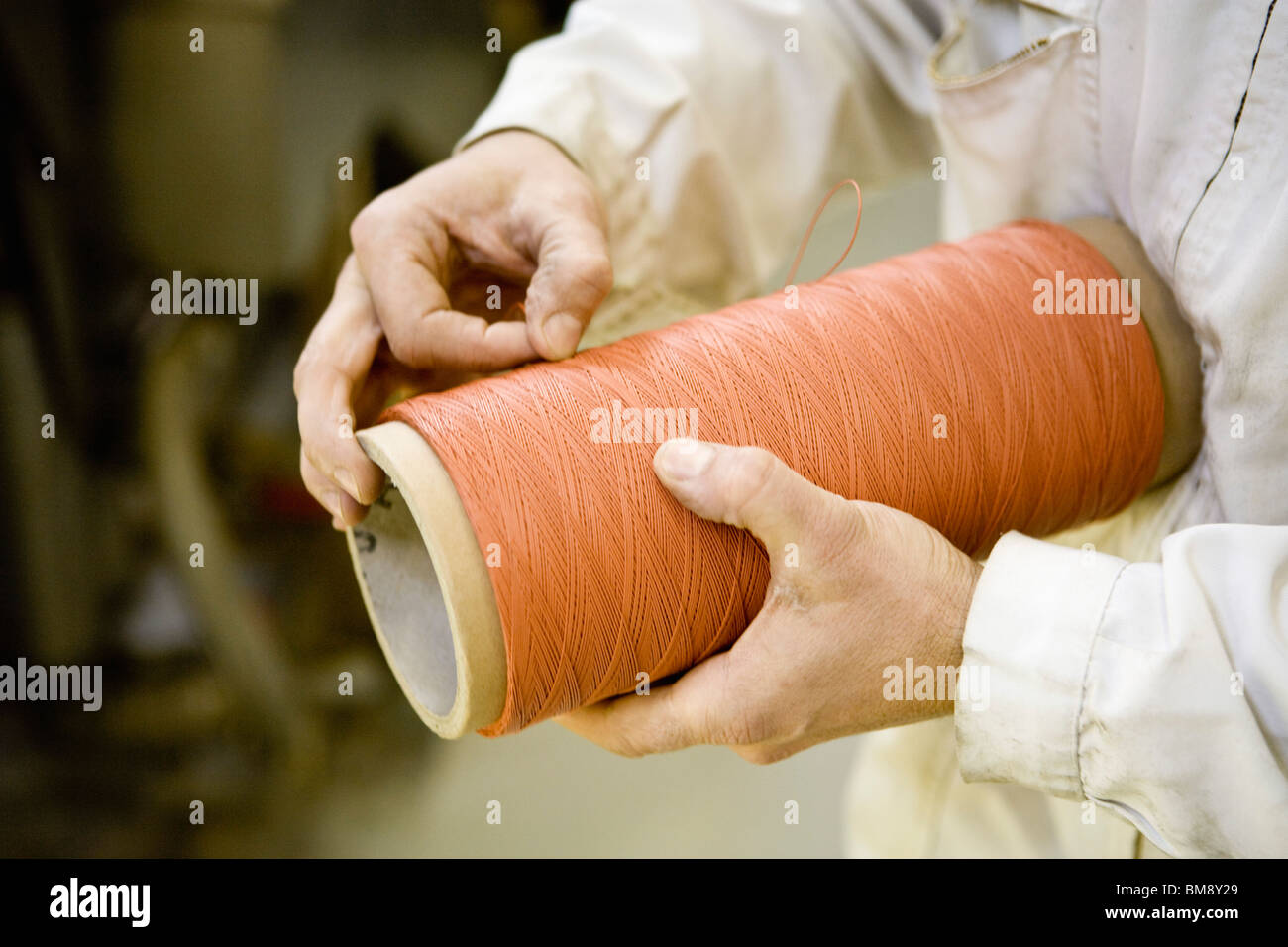 Recyclable composite textile fabrication department of factory, worker performing quality control on thread - Stock Image