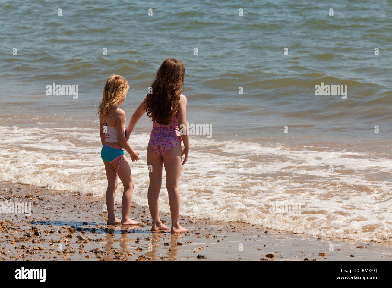 two young girls in swim suits standing together at edge of sea on beach looking out to sea Stock Photo