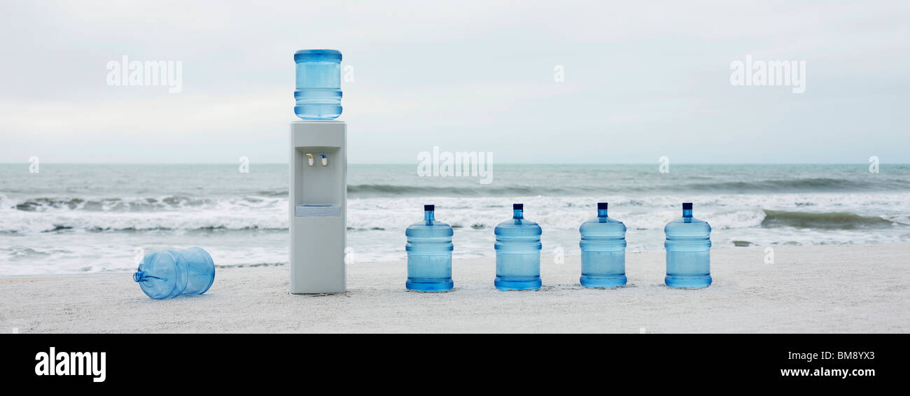 Water cooler and water jugs lined up on beach - Stock Image