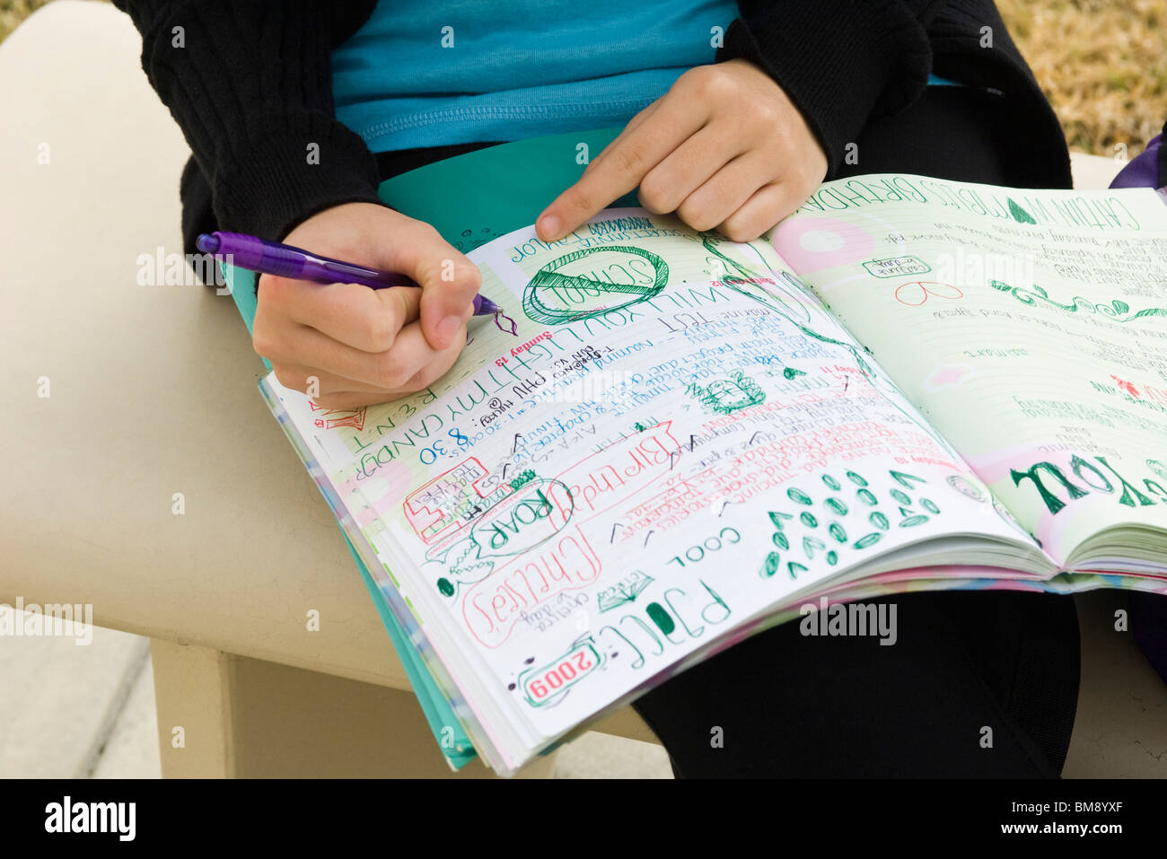 Student writing in notebook illustrated with doodles Stock Photo