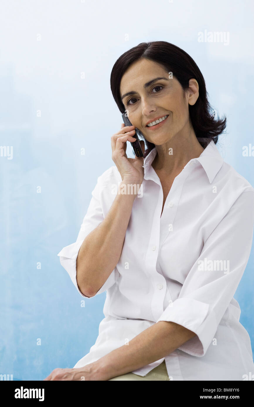 Woman using cell phone, smiling at camera Stock Photo