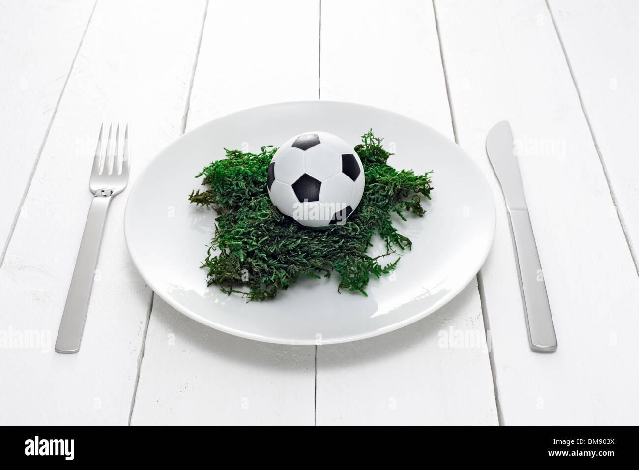 Teller mit Minifussball auf Moos - Stock Image