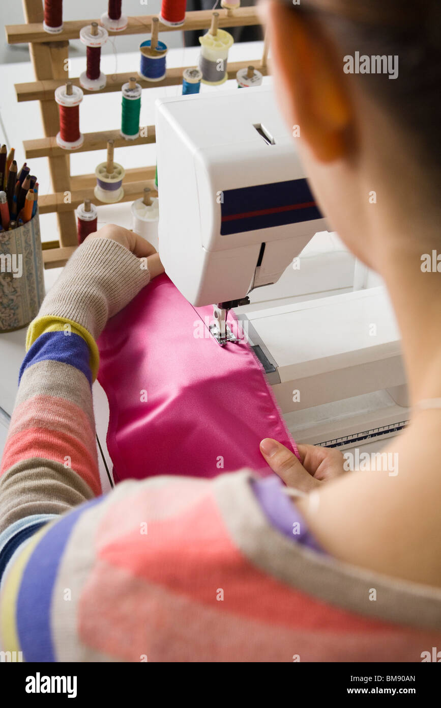 Seamstress sewing on sewing machine - Stock Image