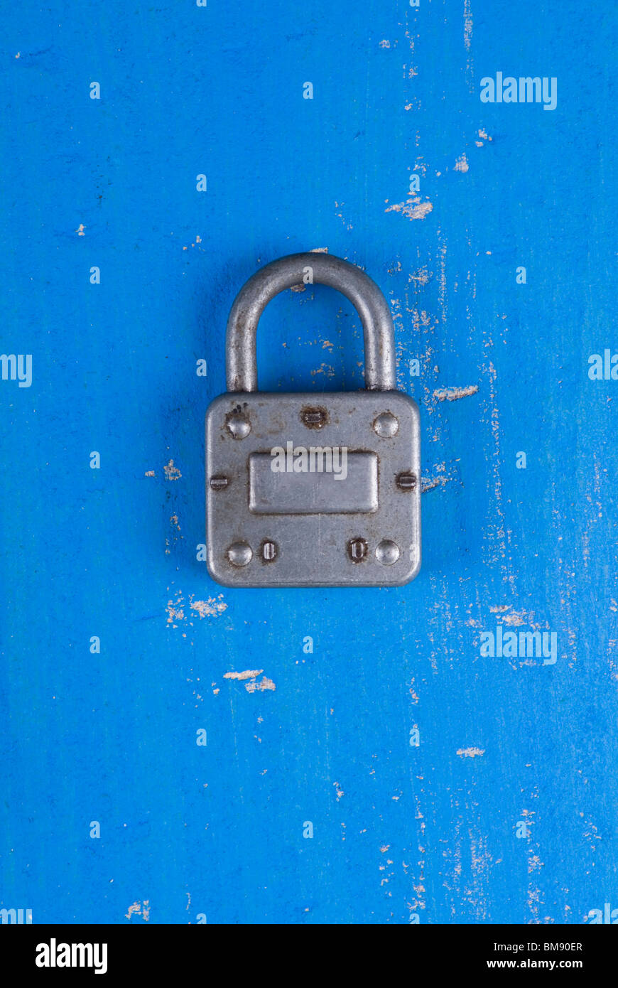 Old fashion silver padlock on a textured blue wooden background - Stock Image