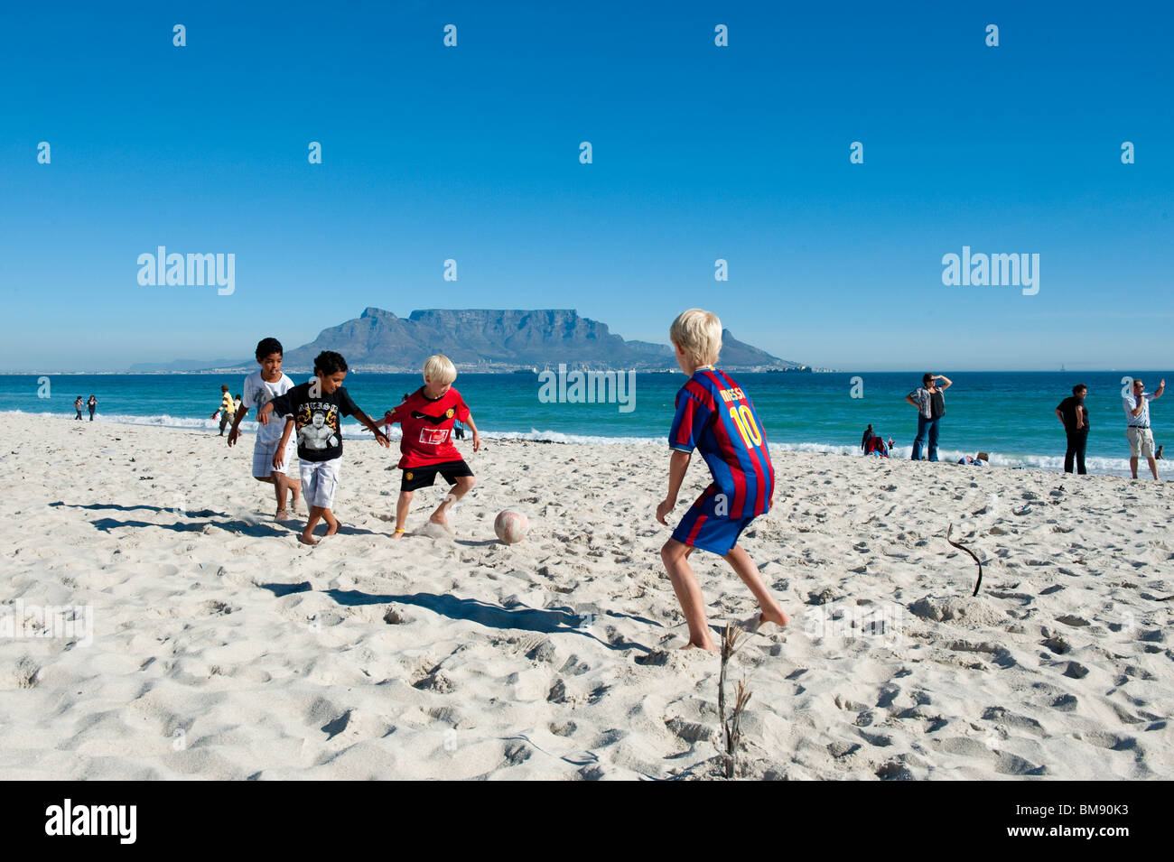 Children playing football on the beach in Bloubergstrand Cape Town South Africa - Stock Image