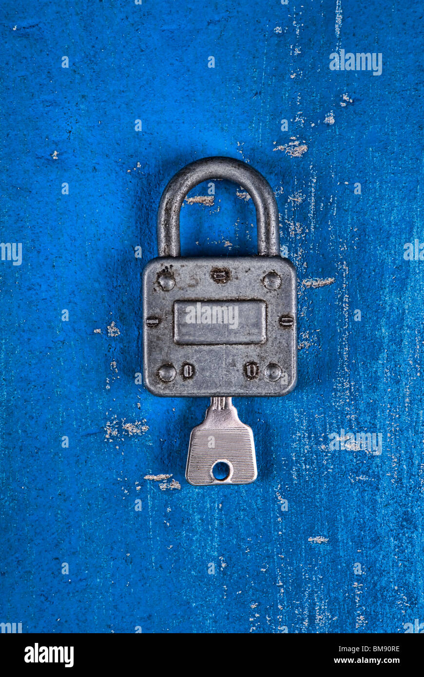 Old fashioned padlock with key on a blue wooden background - Stock Image