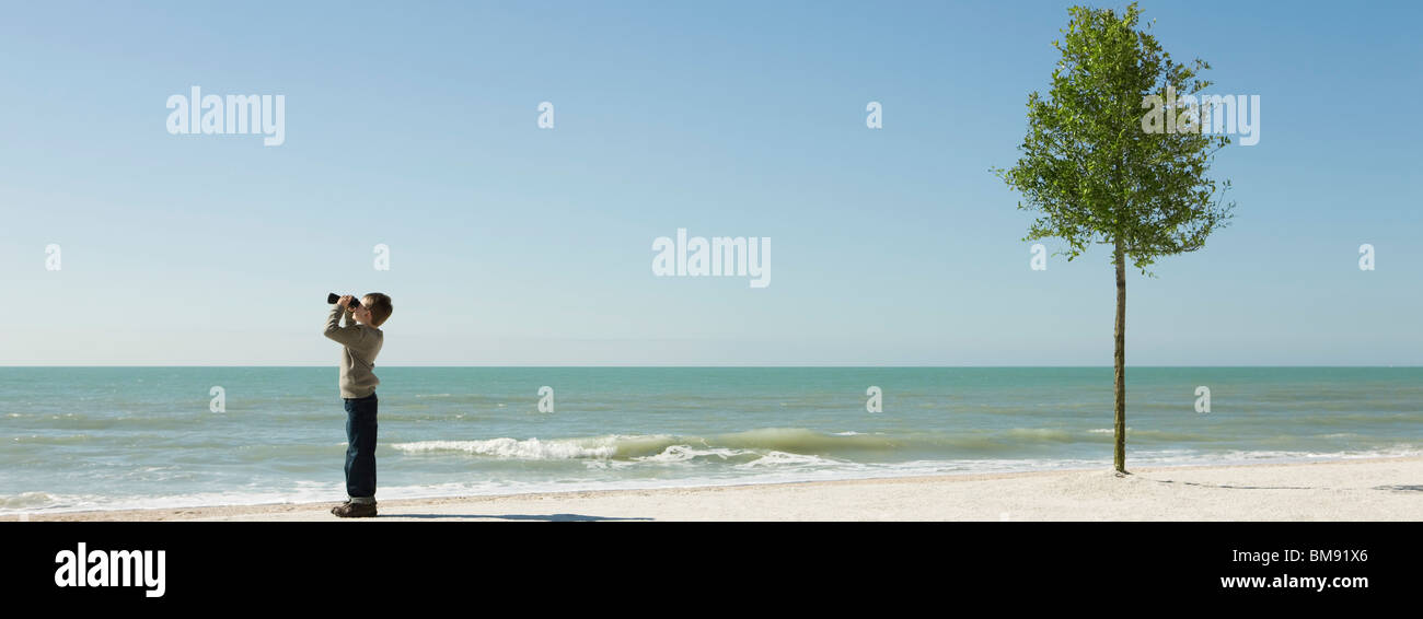 Boy standing on beach, looking at sea with binoculars - Stock Image