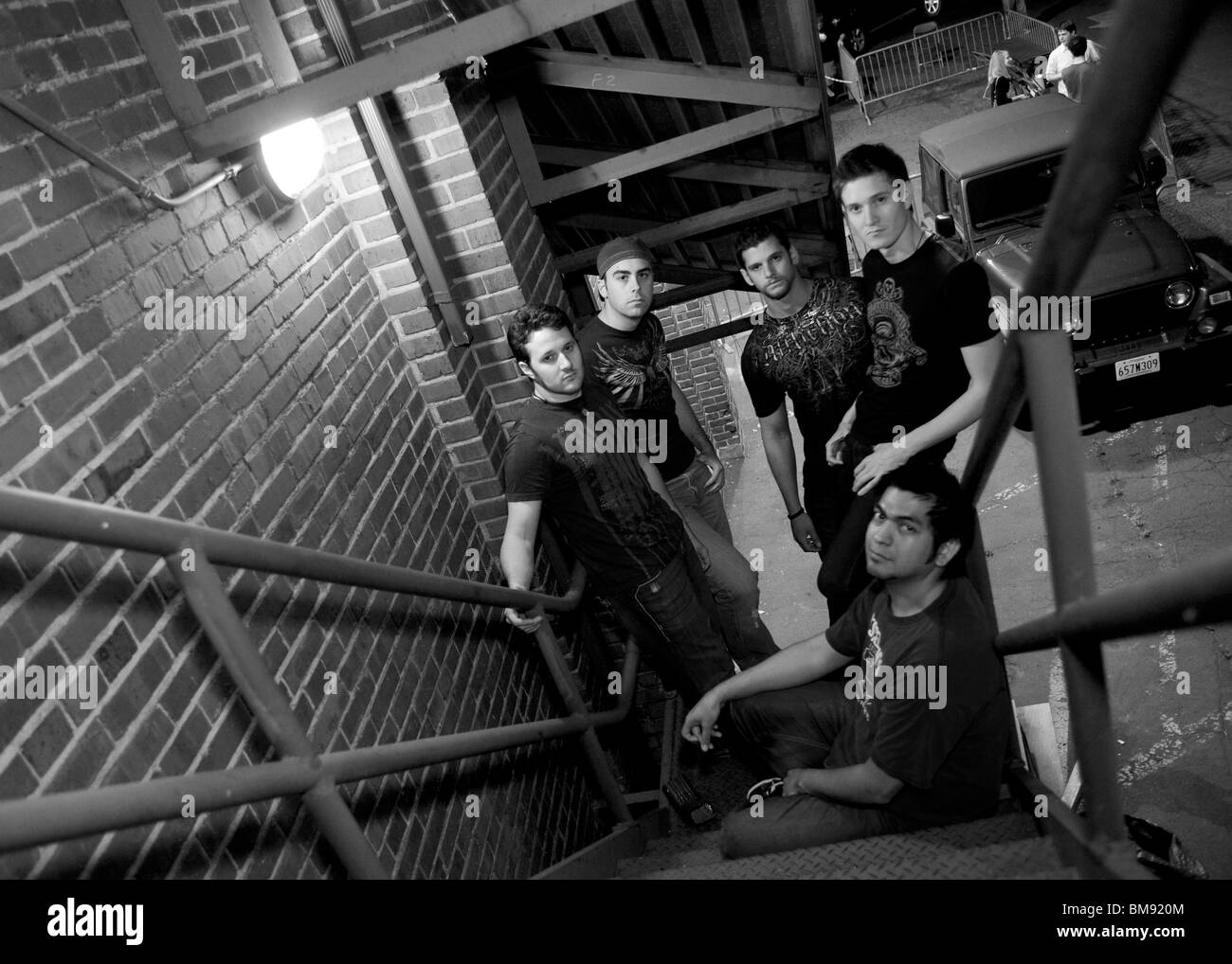 Rock band members promo photo on fire escape stairs - Stock Image