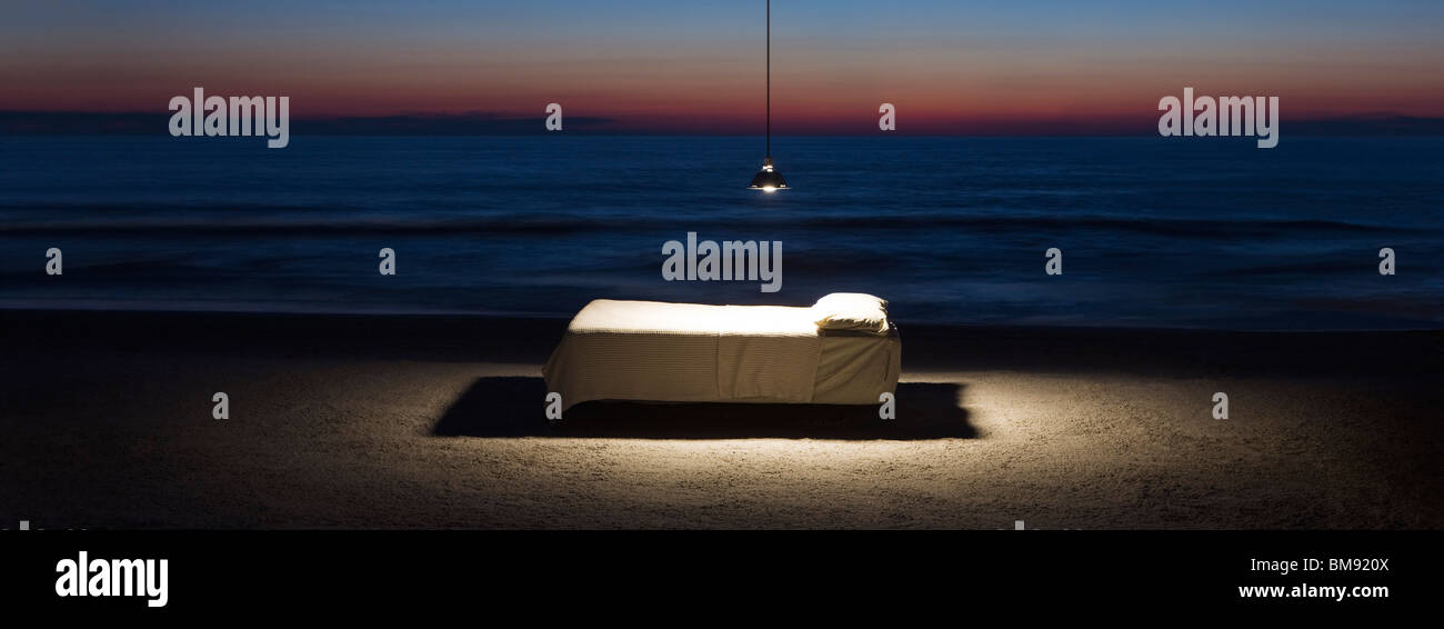 Bed illuminated by hanging lamp on beach - Stock Image