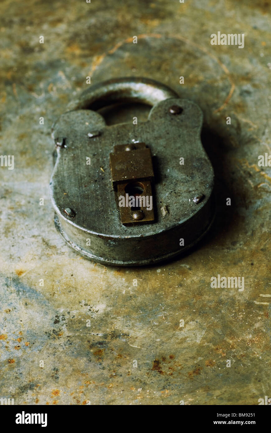 Old fashioned rusty padlock over a grungy background - Stock Image