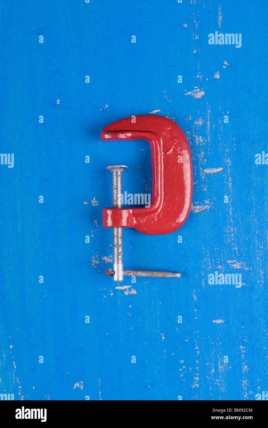 Metal C clamp over a blue wooden background - Stock Image
