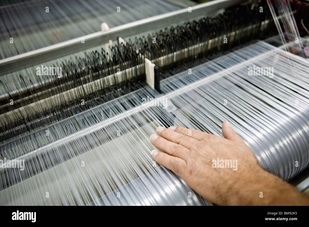 Weaving mill, machinist manually checking thread tension on a loom - Stock Image
