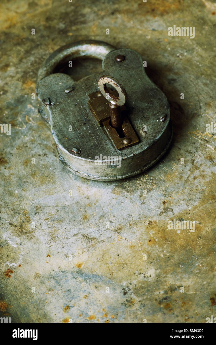 Old fashioned rusty padlock with key over a grungy background - Stock Image