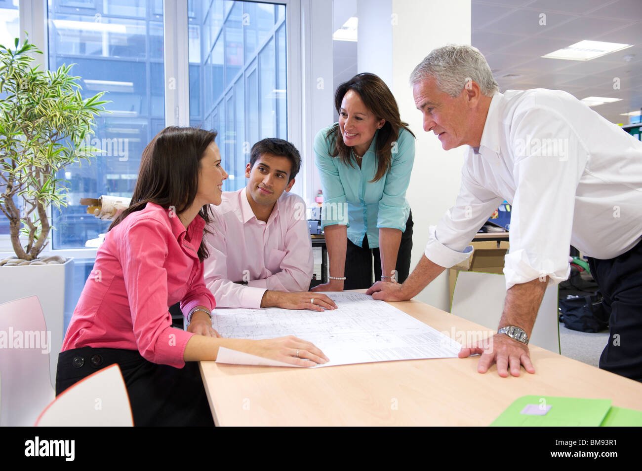 Team meeting to discuss plan drawings at architects office - Stock Image