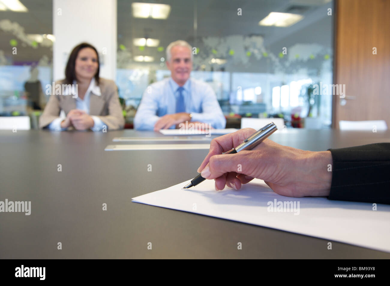 Hand and pen close up in a business meeting - Stock Image