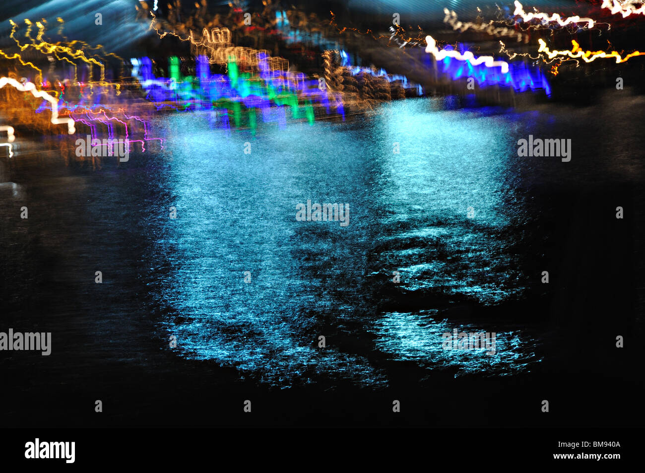 Reflections of neon light on water - Stock Image