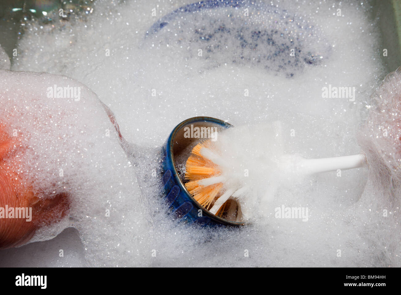 UK, Europe. Person washing up by hand using a brush with soap suds in a bowl of water. - Stock Image