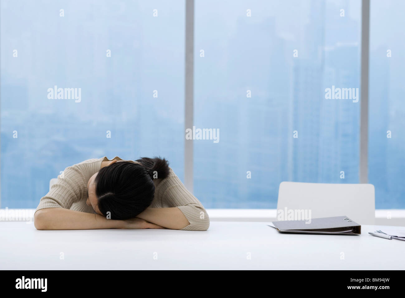 Woman napping at desk in office - Stock Image
