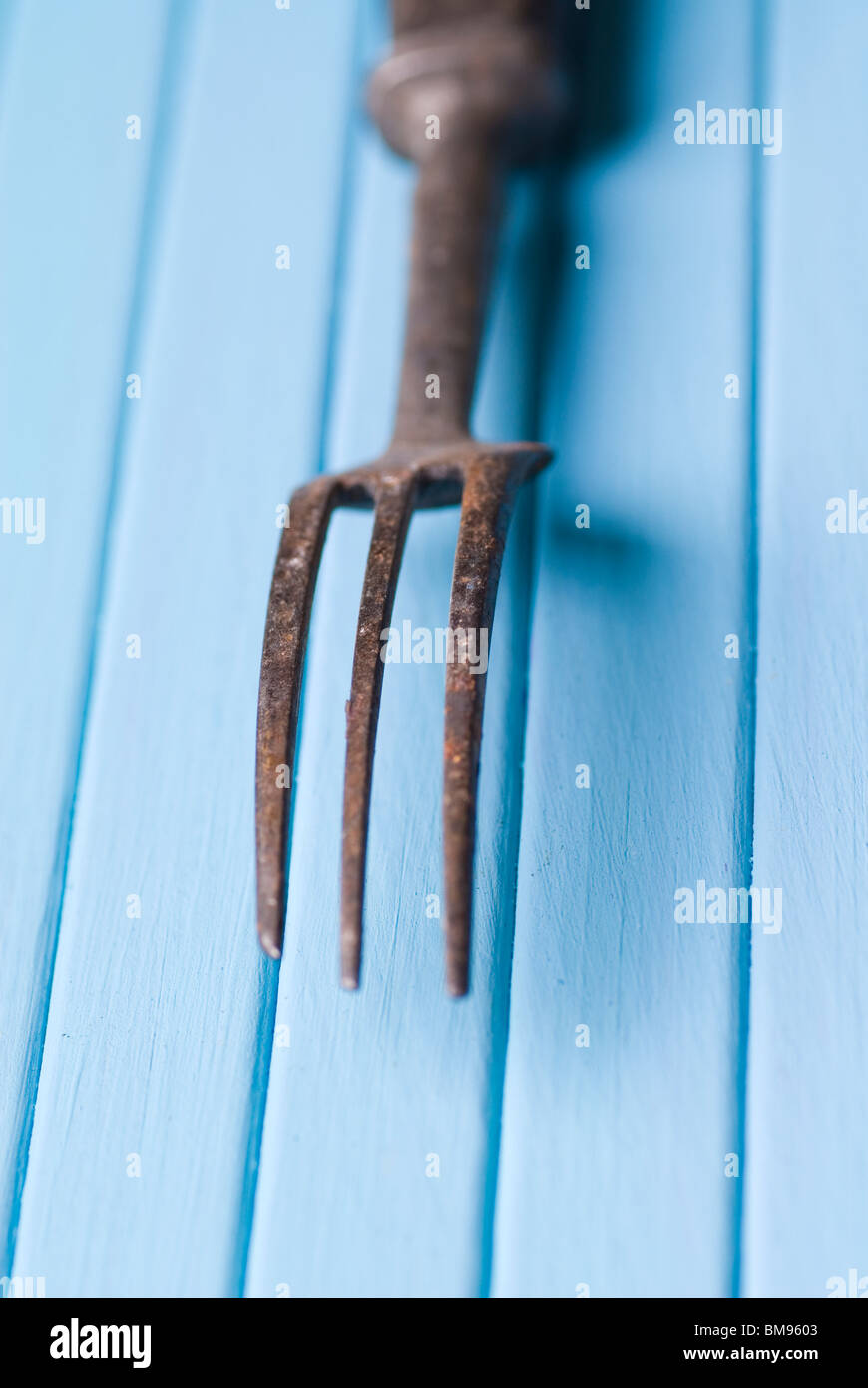 Old fashioned fork rusted over a blue wooden background - Stock Image