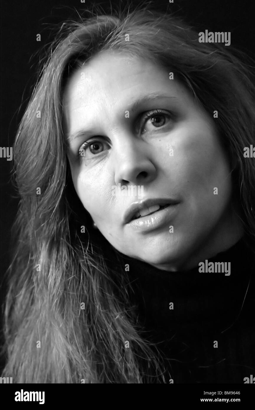 black and white portrait of white woman's face with long hair, her heads is tilted as if listening against black - Stock Image