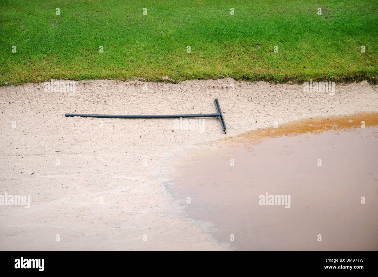 A rake in a waterlogged bunker during a downpour at the Celtic Manor Wales Open 2008 the venue for the 2010 Ryder Stock Photo
