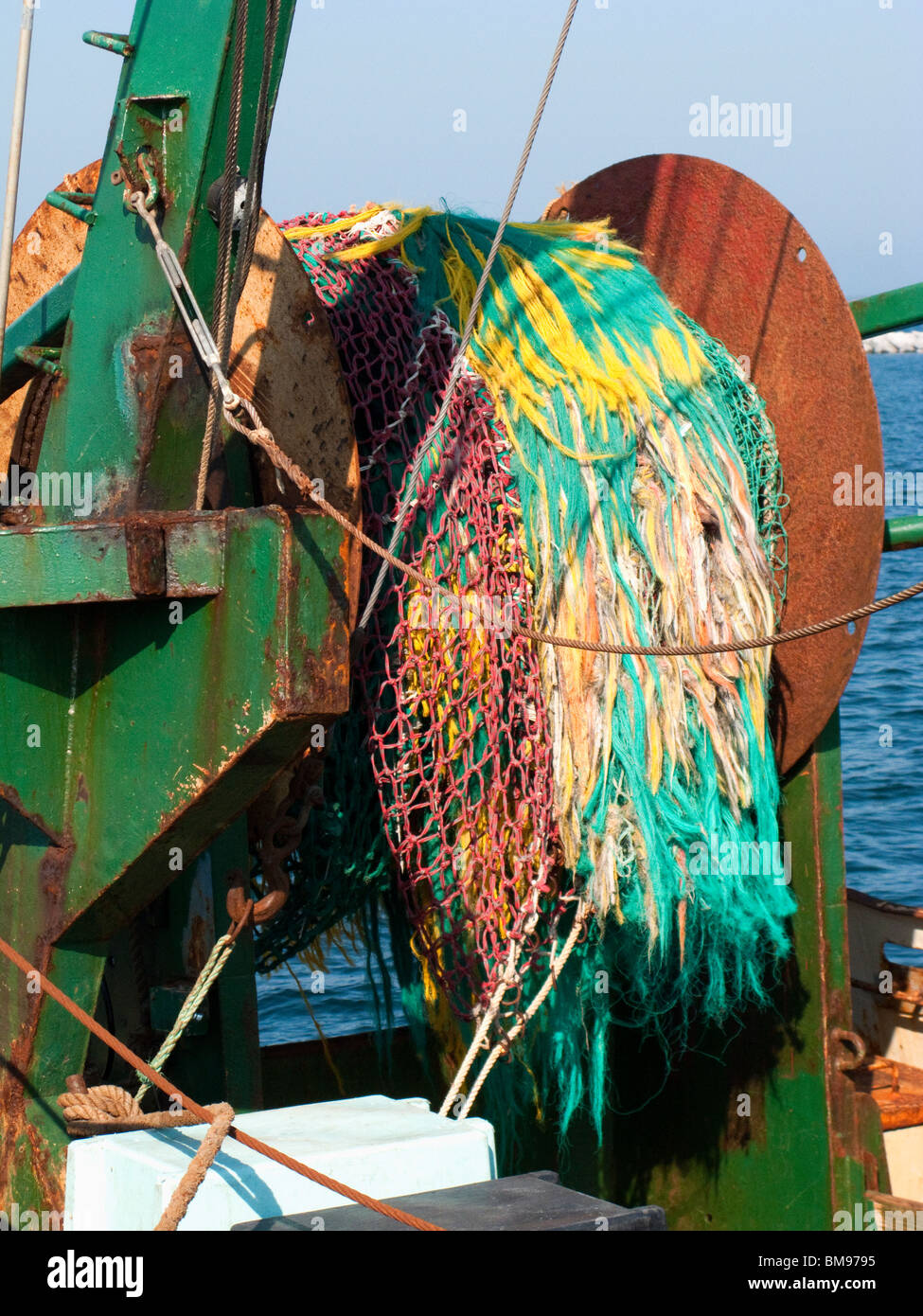 Colorful Net on Back of Fishing Boat Wound Up on Core - Stock Image