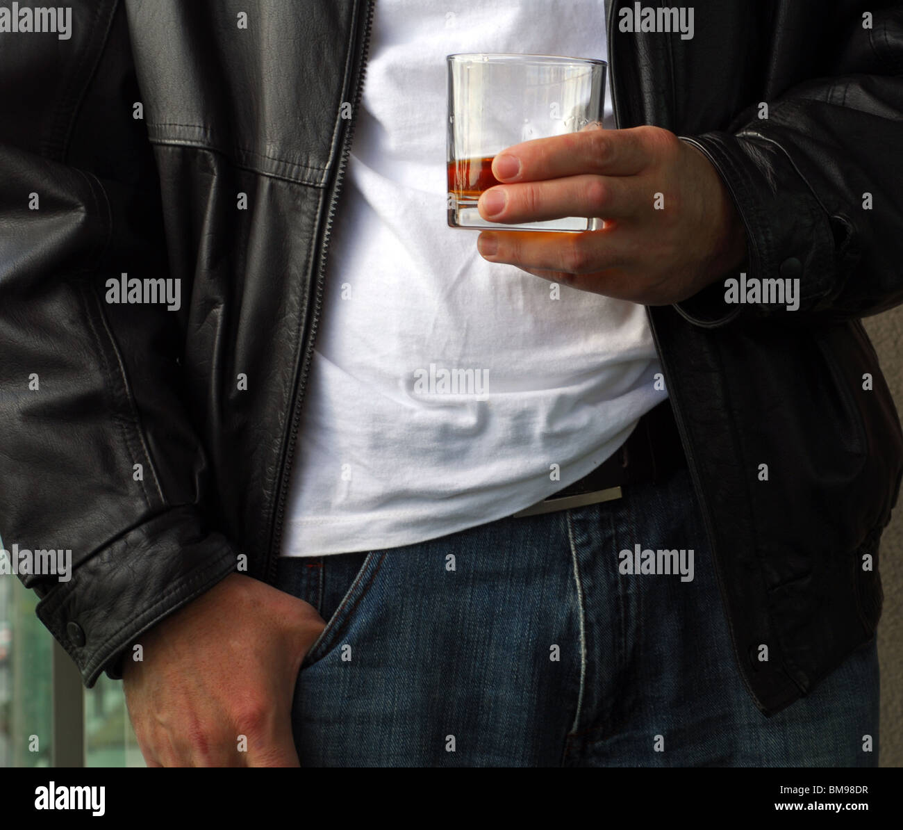 Man holding whiskey extremely close - Stock Image