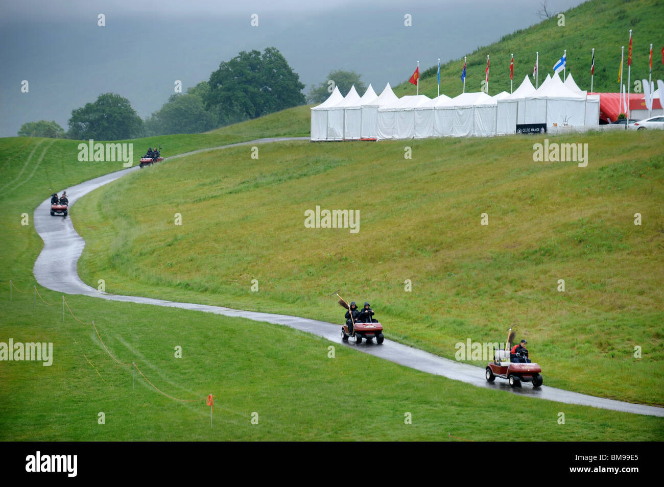 Groundsmen riding on golf buggies head for cover from the rain at the Celtic Manor Wales Open 2008 - Stock Image