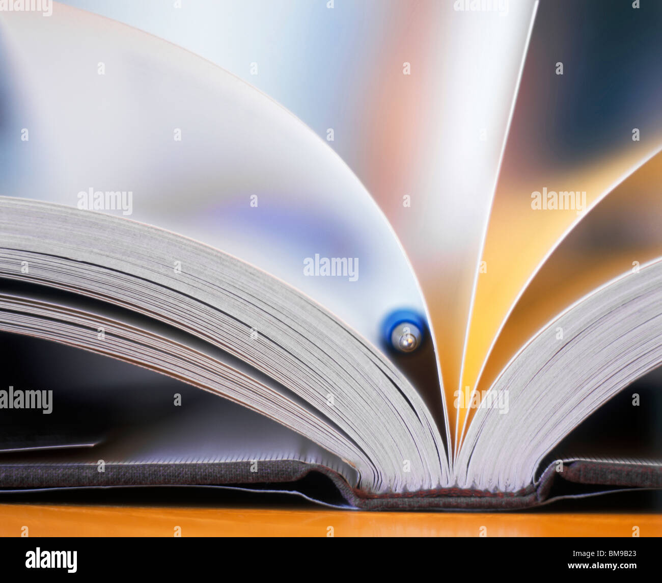 Still-life, An Open, fanned book with pen as Bookmark, close-up - Stock Image
