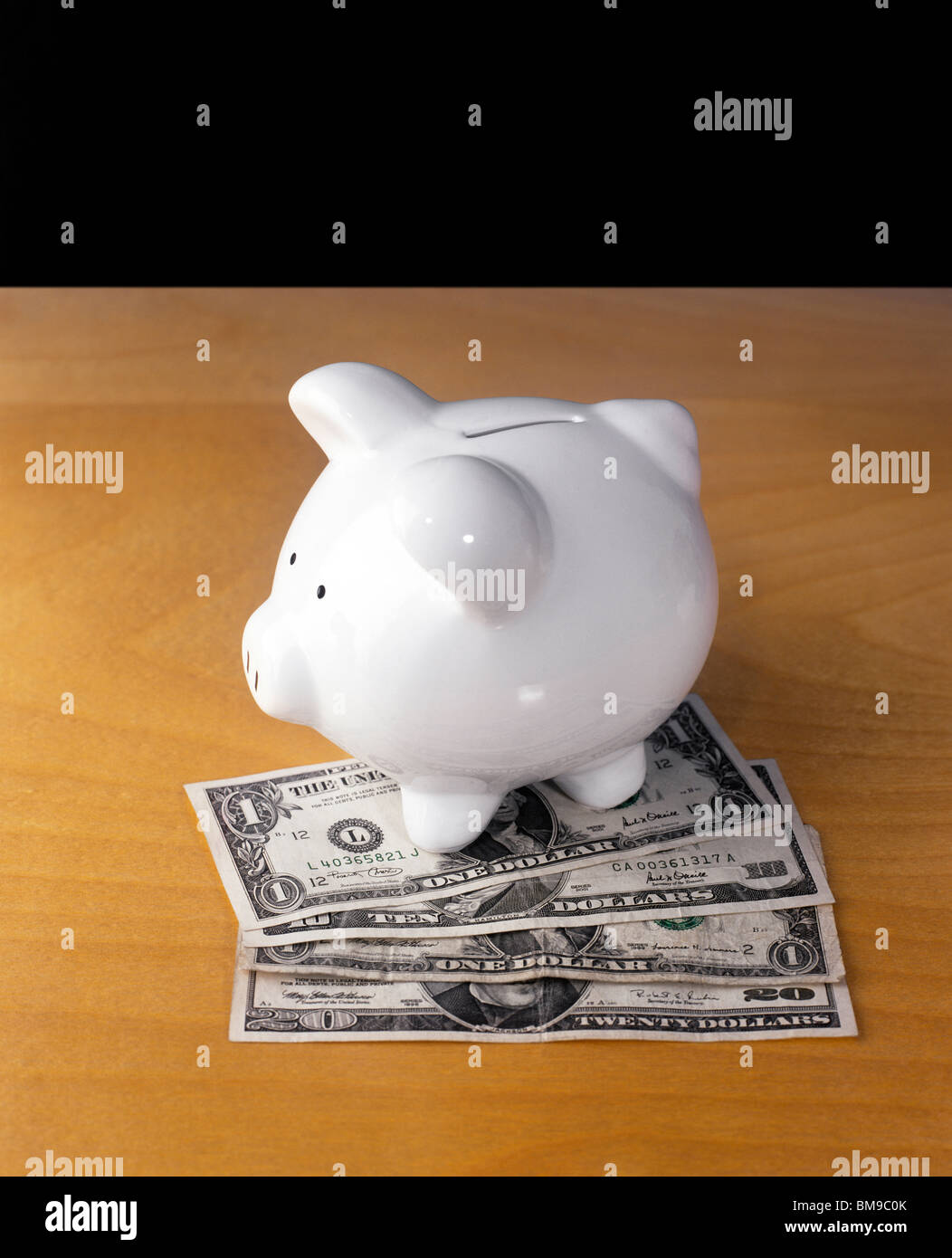 Still-life of a Piggy or coin savings Bank on desk - Stock Image