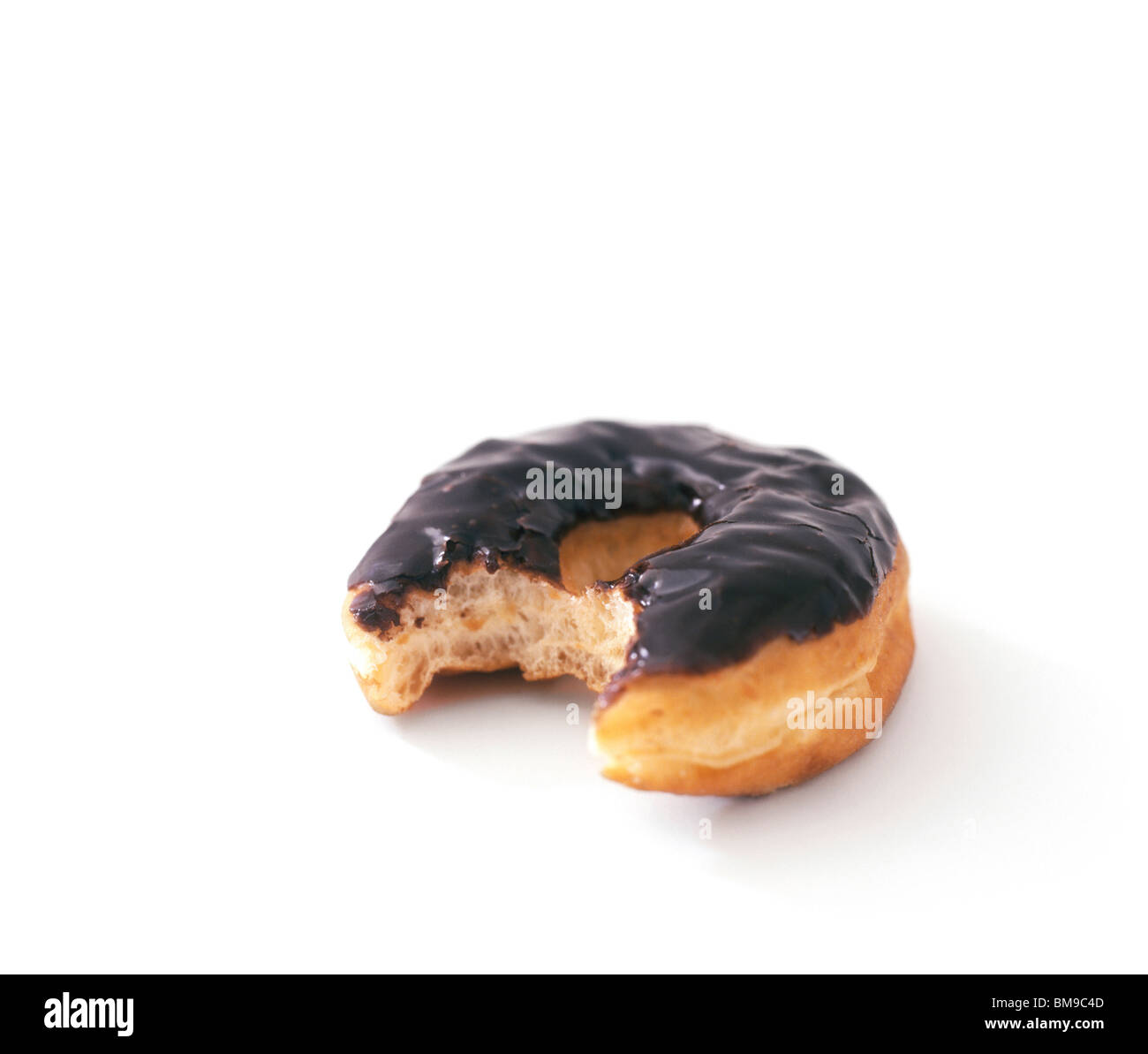 Still-lie of a Chocolate Donut with bite taken out - Stock Image