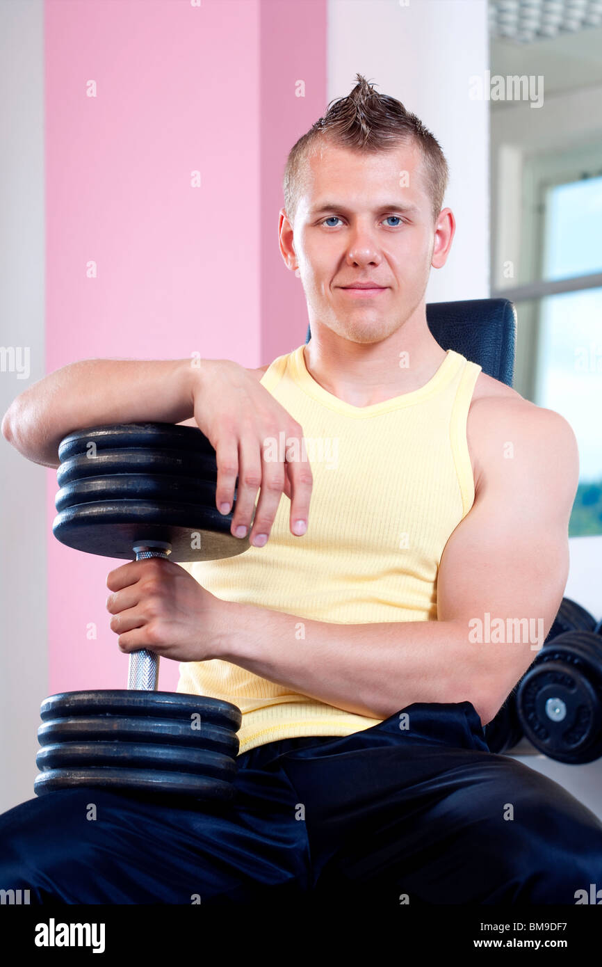 portrait of a young man holding dumbbells in modern gym - Stock Image